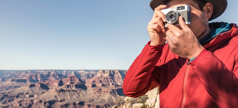 man taking photograph near canyon